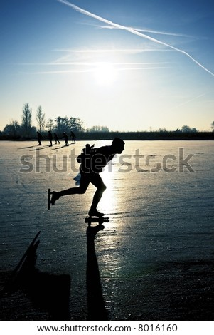 Ice skater at sunset on frozen ice in the fields of the Netherlands - stock photo