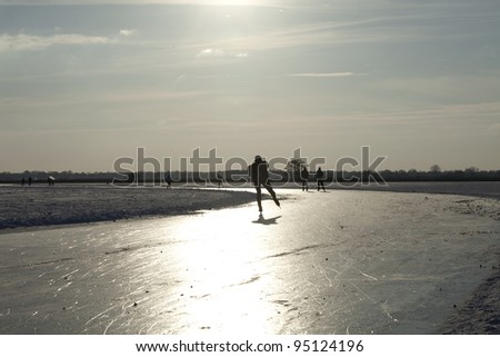 """Ice skaters on frozen lake practicing for the """" round of Duurswold"""" in the north of Holland., 80 km skating race on feb 9 2012. - stock photo"""