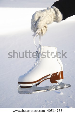 Ice skates. Closeup of female hand holding ice skates outdoors with snow and ice in the background. - stock photo