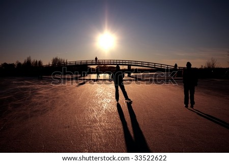 Ice skating at sunset on the canals in the countryside of the Netherlands - stock photo