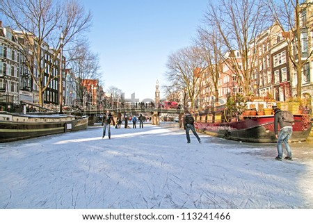 Ice skating on the canals in Amsterdam the Netherlands in winter - stock photo