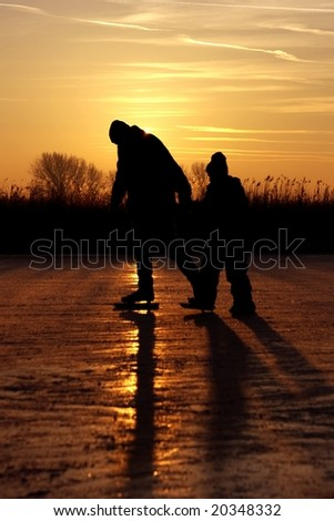 Ice skating with sunset on a frozen lake in the countryside from the Netherlands - stock photo