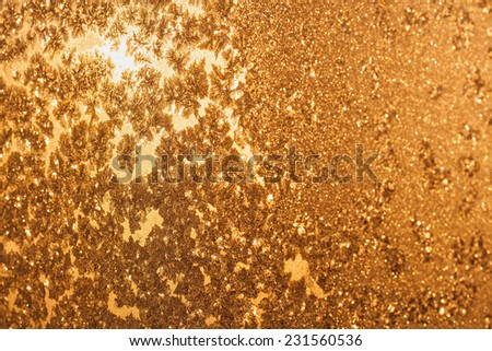 Ice snowflakes and frost pattern over the sun on frozen Christmas winter window. Colored in yellow or gold tone. Selective focus at center with blur edges of image - stock photo