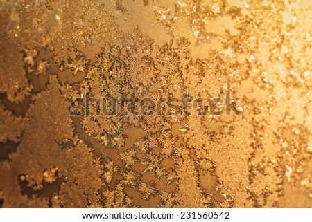 Ice snowflakes and frost pattern with sunlight on Christmas winter frozen window. Colored in yellow or gold tone. Selective focus with blur edges of image - stock photo