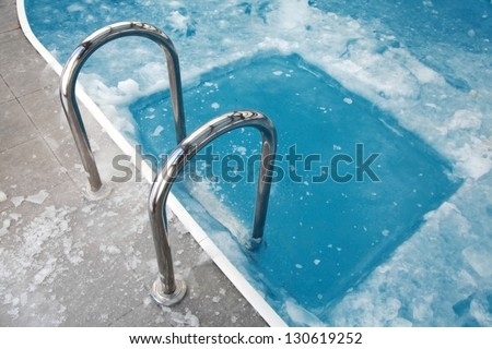 Ice swimming theme. Steps in the frozen blue pool ice-hole - stock photo