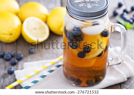Ice tea in mason jar mug with lemon and blueberries refreshing in hot summer day - stock photo