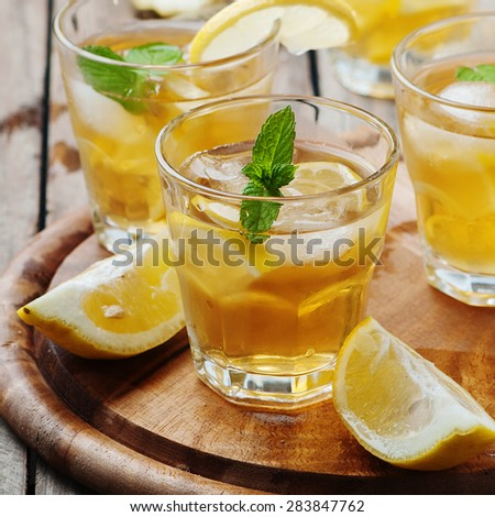 Ice tea with lemon and mint, selective focus and square image - stock photo