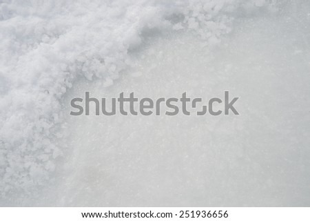 Ice texture on outdoor rink with snow in the corner - stock photo