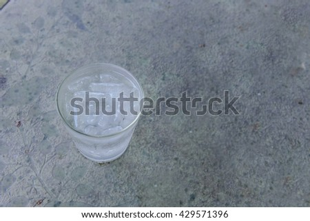 Ice water in a glass on cement table - stock photo