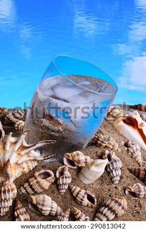 Ice water in the sand against the shell - stock photo