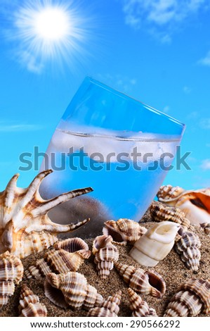 Ice water in the sand against the shells and blue sky - stock photo