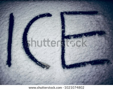 Ice written outside on car while snowing