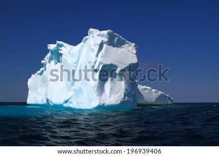 Iceberg after traveling 1600 km from Western Greenland to Iceberg Alley around East coasts of Labrador and Newfoundland already loss big part of its ice mass by melting and breaking on small pieces  - stock photo