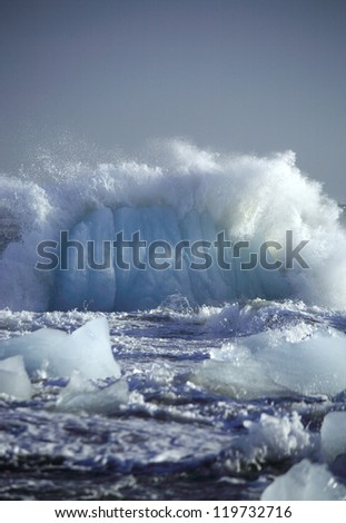 Iceberg being smashed up by the sea Iceland - stock photo