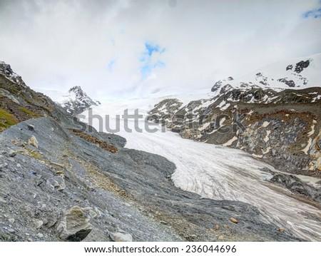 Iceberg Findelgletscher in stony valley bellow Adlerhorn massif, Zermatt region, Switzerland. The rest of ice at end of autumn, first snow on rocky peaks above  - stock photo