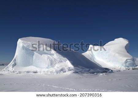 Iceberg frozen in the ocean off the Antarctic Peninsula in winter sunny day - stock photo