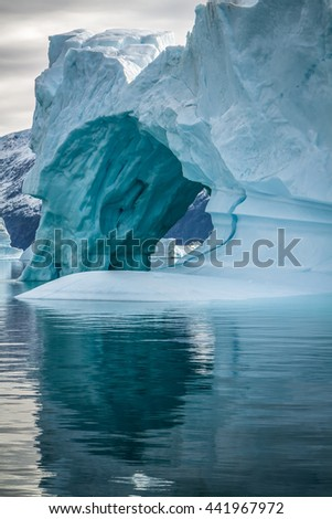 Iceberg in Greenland.  This iceberg has several ice caves. - stock photo