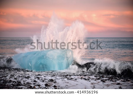 Iceberg on the black volcanic beach during sunset being hit by a violent wave - stock photo