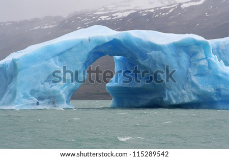 iceberg with an arch of ice floating in argentino lake, in the argentinian national park of glaciers - stock photo