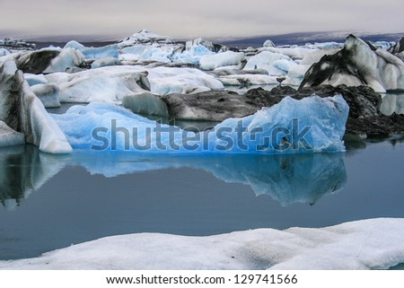 iceberg with reflection in water - stock photo