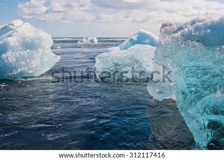 Icebergs are floating in the ocean. Seagulls are flying around. - stock photo