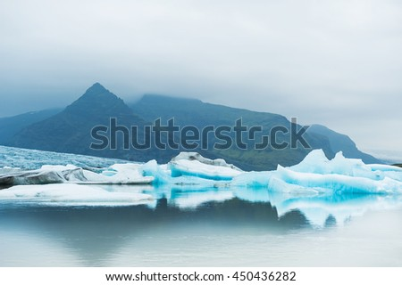 Icebergs in the glacial lake with mountain views. Vatnajokull glacier, Fjallsarlon lagoon, south Iceland
