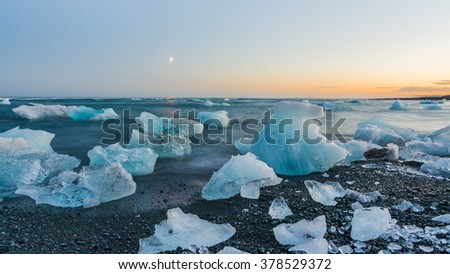 Icebergs on a black beach at sunset in Jokulsarlon, Iceland