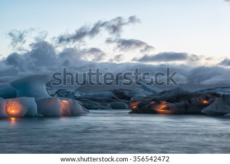 Icebergs with candles, Jokulsarlon ice lagoon before annual firework show, Iceland - stock photo