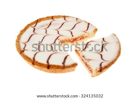 Iced Bakewell tart with a slice cut out isolated against white - stock photo