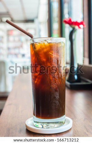 Iced black coffee on the wooden table in coffee cafe.