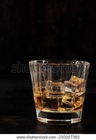 Iced bourbon or whiskey in a glass tumbler on a dark background with vertical copyspace - stock photo