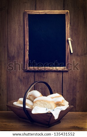 Iced buns in basket with blank menu board - stock photo