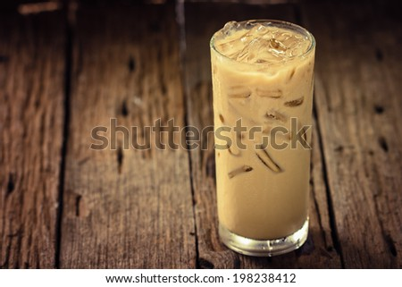Iced coffee in glass on wooden - stock photo
