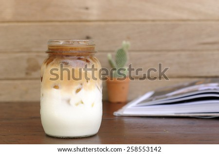 Iced coffee in jar on wooden table.  - stock photo