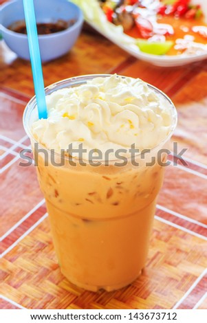 Iced coffee in take away cup on tablecloth. - stock photo