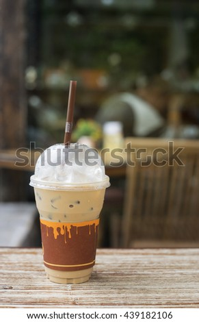 Iced coffee in takeaway cup on wood table with blurred coffee cafe background,Selective focus - stock photo