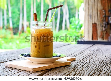 Iced coffee latte in glass on wood table. - stock photo
