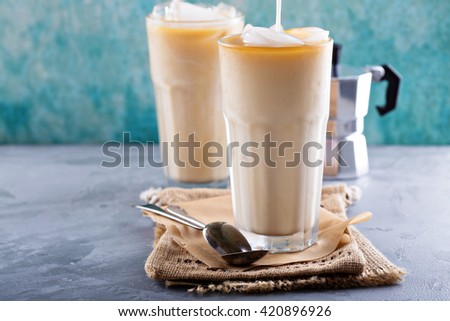 Iced coffee with milk in tall glasses on the table - stock photo