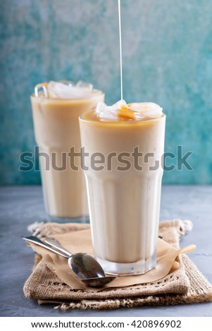 Iced coffee with milk in tall glasses on the table with caramel syrup poured over - stock photo