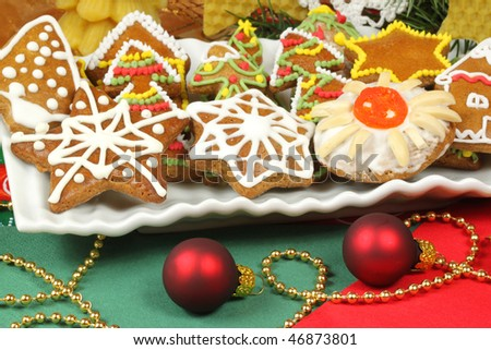 Iced colorful gingerbread Christmas cookies on plate with decoration - stock photo