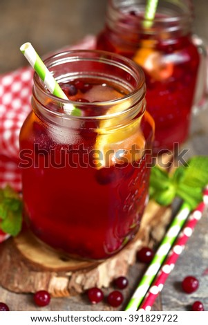 Iced cranberry tea with orange in a mason jar on rustic background. - stock photo