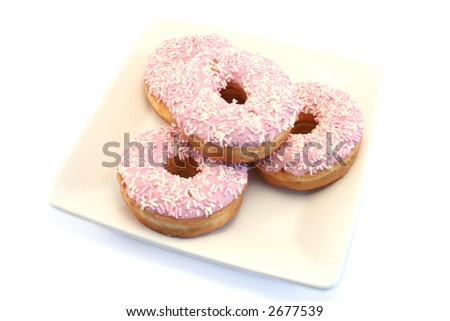 Iced donuts and sprinkles on a cream china plate - stock photo