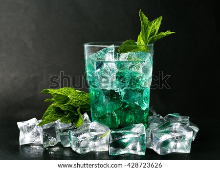 Iced green peppermint syrup with tonic water and ice cubes - stock photo