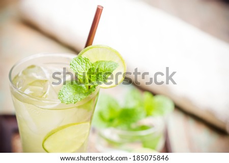 Iced green tea with lime garnish and ice cube - stock photo