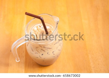Iced Latte Coffee and glass jug on the wood floor table