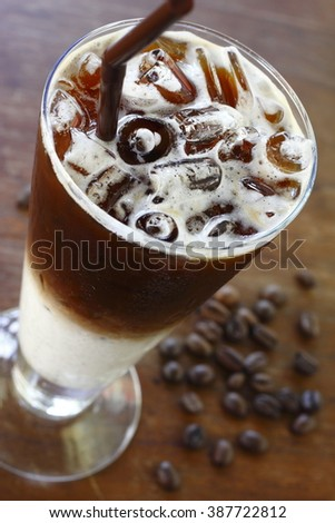 iced latte on wooden table. glass of iced latte. iced coffee. - stock photo