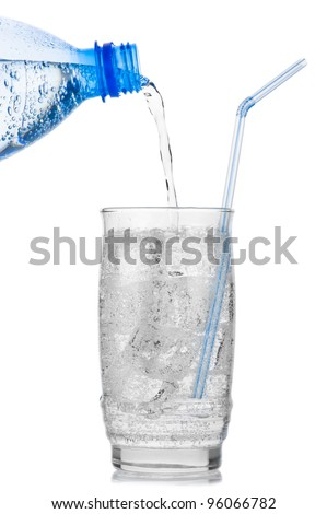 Iced mineral water pouring from plastic bottle into a glass with ice cubes and straw over white background - stock photo