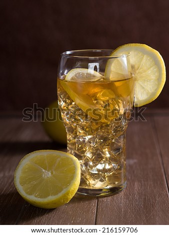 Iced tea with lemon and ice cubes in a glass