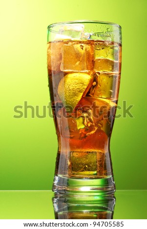 Iced tea with lemon and lime on green background - stock photo