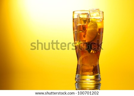 Iced tea with lemon and lime on yelow background - stock photo